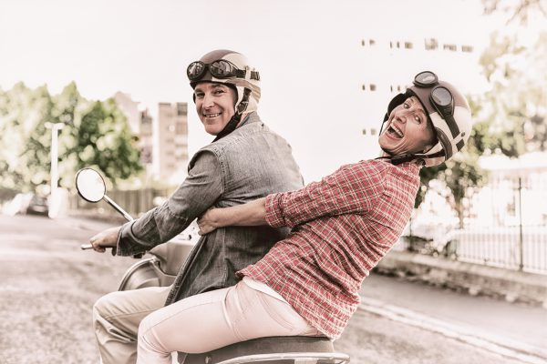 retired couple actively riding a scooter